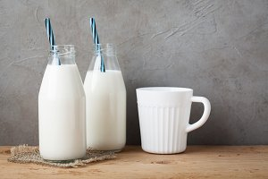 Two bottles of milk on dark background with copy space