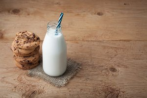 Bottle with milk and chocolate chip cookies on dark background. Top view
