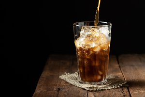 Ice coffee in a tall glass over and coffee beans on a old rustic wooden table. Cold summer drink on a dark background with copy space. The process of pouring drink from a coffee pot into a glass