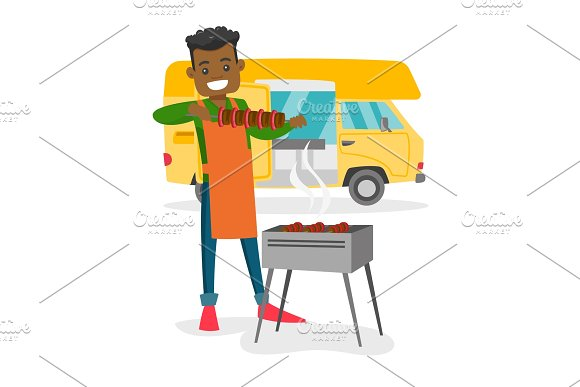 Young Man Barbecuing Meat In Front Of Camper Van