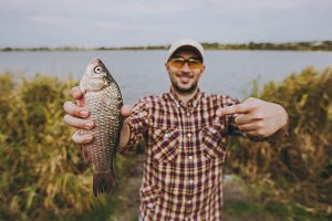 Young unshaven man in checkered shirt, cap and sunglasses caught fish, shows it and points with a finger on it on shore of lake on background of water and reeds. Lifestyle, fisherman leisure concept