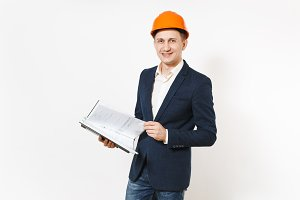 Young smiling businessman in dark suit, protective construction orange helmet holding black folder for papers document isolated on white background. Male worker for advertisement. Business concept.