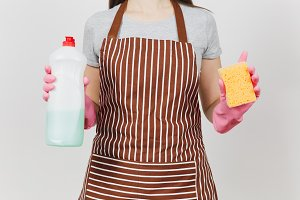 Close up cropped portrait housewife in pink gloves, striped brown apron isolated on white background. Woman holding bottle with cleaner liquid for washing dishes, sponge. Copy space for advertisement.