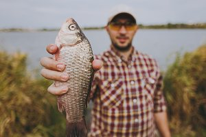 Close up Young unshaven man in checkered shirt, cap and sunglasses caught fish, shows it on shore of lake on background of water, shrubs and reeds. Lifestyle, recreation, fisherman leisure concept