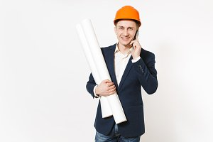 Young smiling businessman in dark suit, protective construction orange helmet holds blueprints plans, talks on mobile phone isolated on white background. Male worker, advertisement. Business concept.