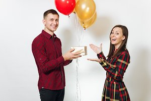 Beautiful young happy smiling couple in love. Woman and man holding golden gift boxes with present and red, yellow balloons, celebrating birthday, on white background isolated. Holiday, party concept.
