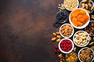 Nuts and dried fruits assortment on stone table top view.