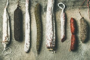 Flat-lay of variety of Spanish or Italian cured meat sausages