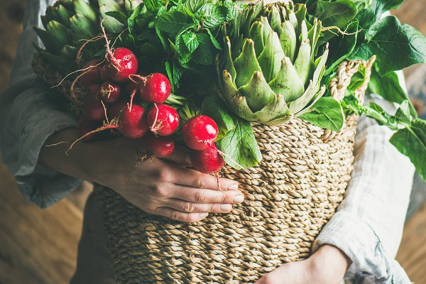 Female farmer holding basket with f…