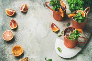 Blood orange Moscow mule alcohol cocktails, concrete background, copy space