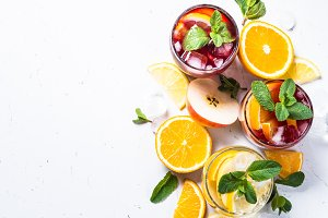 White, pink and red sangria with fruit, ice and mint top view.