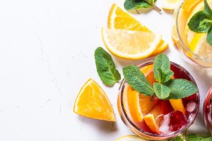 White, pink and red sangria with fruit, ice and mint.