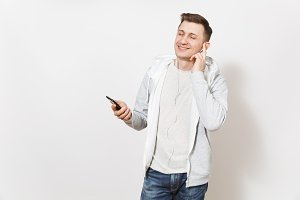 Young handsome smiling man student in t-shirt, blue jeans and light sweatshirt listening to music on earphones on mobile phone and enjoys in studio on white background. Concept of emotions, good mood.