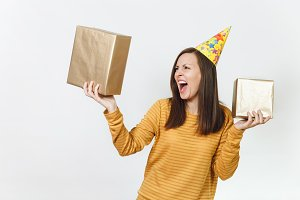 Beautiful caucasian angry young woman in yellow clothes, birthday party hat holding golden gift boxes with present, celebrating and screaming on holiday on white background isolated for advertisement.