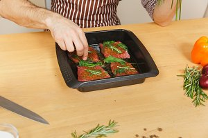 Close up man in apron sitting at table, putting herbs, rosemary, basil in black baking tray, cooking at home, preparing meat stake from pork, beef or lamb, in light kitchen with wooden surface.