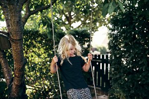 Cute little blonde girl playing on a tree swing outside