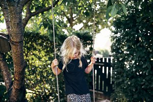 Little blonde girl playing on a tree swing outside
