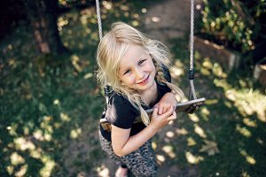 Smiling little girl playing alone on a swing outside