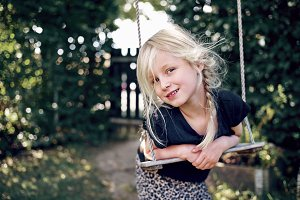 Adorable little girl smiling while playing on a tree swing