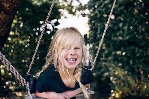 Laughing little girl playing on a tree swing outdoors