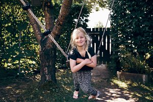 Cute little girl smiling while playing on a tree swing