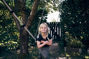 Smiling little girl playing on a tree swing outdoors