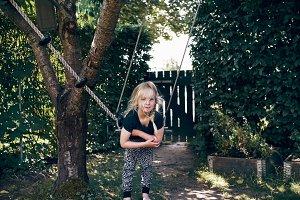 Cute little girl hanging on a tree swing outside