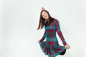 Beautiful caucasian fun young happy woman in plaid dress and birthday party hat with shy charming smile and brown hair, celebrating and enjoying holiday on white background isolated for advertisement.