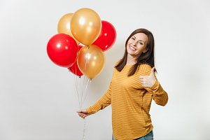Beautiful young happy woman in yellow clothes with charming smile, red, golden balloons, celebrating birthday, showing thumb up on white background isolated for advertisement. Holiday, party concept.