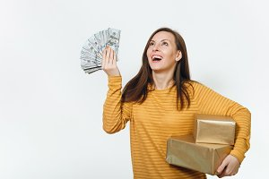 Beautiful caucasian fun young happy birthday woman in yellow clothes holding wad of cash money, golden gift boxes with present, celebrating holiday party on white background isolated for advertisement