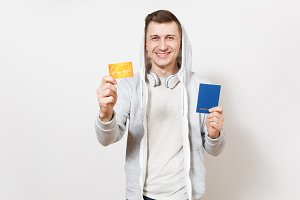 Young handsome smiling happy man in t-shirt, light sweatshirt with hood with headphones holds international passport and credit card in hands isolated on white background. Concept of travel, tourism