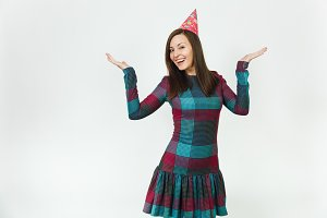 Beautiful young happy woman in plaid dress, birthday party hat with shy charming smile and brown hair, celebrating and enjoying holiday on white background isolated, spreading hands for advertisement.