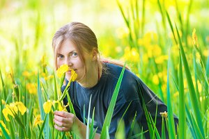Pretty blond woman smells flowers
