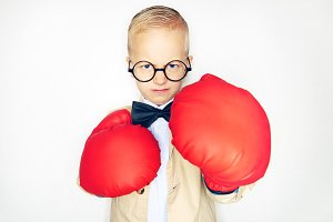 Little boy in suit and boxing gloves
