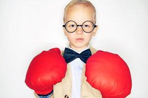 Little kid in boxing gloves in studio