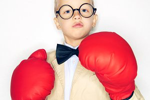 Boy in suit posing with boxing gloves