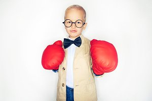 Boy in suit and boxing gloves posing