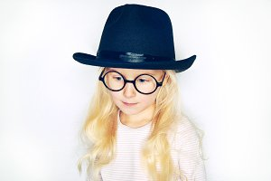 Little girl in hat and glasses posing