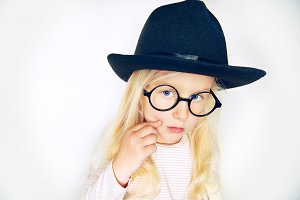Little stylish girl in hat and glasses