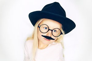 Little blonde girl in hat with moustache