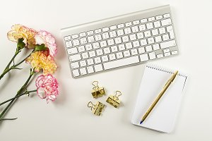 Background of white and pink flowers, yellow flowers, empty notebook next to pen and computer keyboard on white background. Copy space. Mockup.