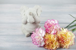 Flowers of various colors next to elephant figure on wooden table. Decor.