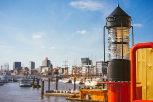 Red light lantern in HafenCity. ght. Port piers with ships and yacht at anchor in background. Hamburg, Germany