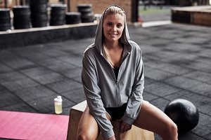Smiling young woman in sportswear sitting at the gym
