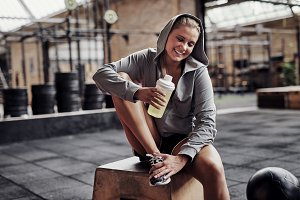 Smiling young woman drinking water while sitting in a gym