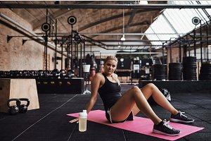 Young woman sitting on a gym floor after working out