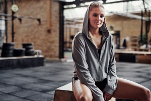 Smiling young woman in sportswear sitting on a gym box