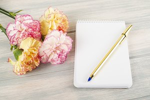 Flowers of various colors next to empty notebook and pen on wooden table. Mockup. Copy space.