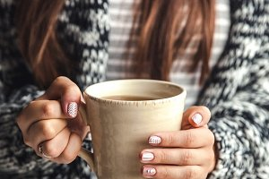Girl's hands holding a cup of coffee