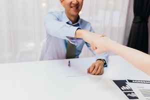 Happy and Smiling businessman  in suit giving fist bump in company office - friendship trust and successful contract concept